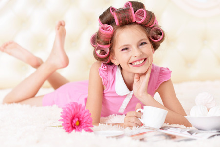 portrait of happy Little pretty girl   in hair curlers with tea Stock Photo