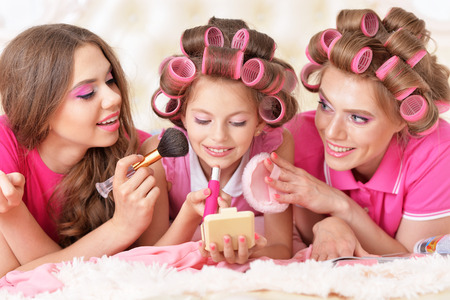 glamour girl: portrait of happy  Mother and  daughters in hair curlers  at home Stock Photo