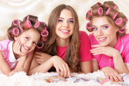 glamour makeup: portrait of happy  Mother and  daughters in hair curlers  at home Stock Photo