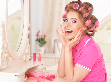 portrait of Beautiful woman in hair curlers near mirror