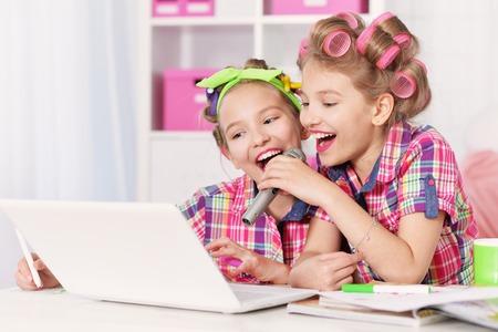 hair curlers: Cute  tweenie girls  in hair curlers  with laptop ,singing in karaoke at home