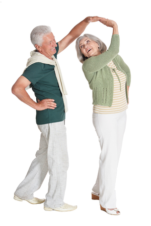 Elegant elderly couple dancing on white background