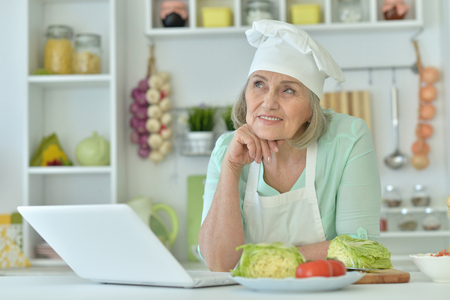 Senior woman portrait at kitchen  with laptop Stock Photo