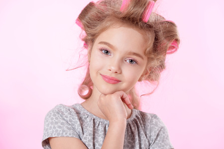 glamour makeup: portrait of happy Little pretty girl   in hair curlers in studio