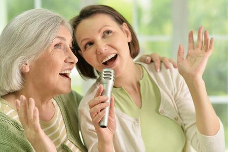 Portret van het Hogere vrouw met dochter zingen op microfoon thuis Stockfoto
