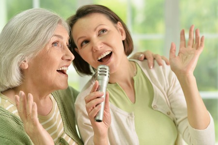 Portrait of Senior woman with daughter singing on microphone at home Archivio Fotografico