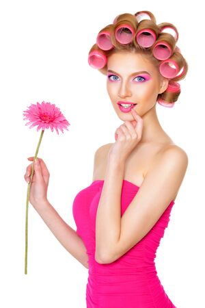 Portrait der schönen Frau im rosafarbenen Kleid mit Lockenwickler im Studio