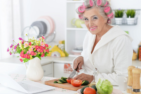 hair rollers: Senior woman in  hair rollers at kitchen with laptop and vegetables