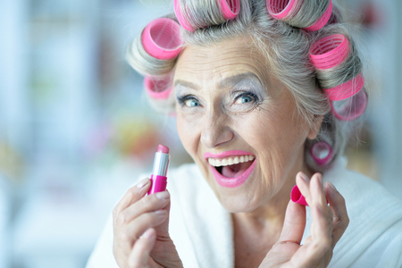 hair rollers: Senior woman in  hair rollers with lipstick at home Stock Photo