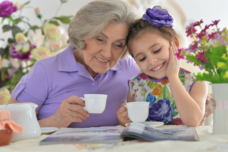 the grand daughter: Old woman with a young girl drinking tea and reading magazine