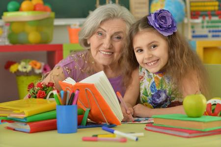Roztomilá holčička dělat domácí úkol s babičkou