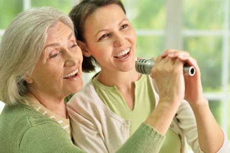 microfono antiguo: Retrato de la mujer mayor con el canto en el micrófono de la hija en el hogar