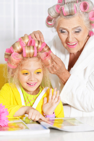 Senior woman and granddaughter doing hairstyle at home