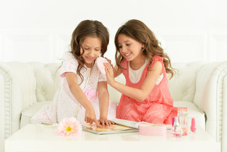 preadolescent: Cute   girls with magazine and cosmetics  at home