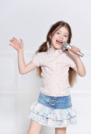 portret van schattig klein meisje in een prachtige jurk zingen