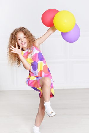 portrait of cute little girl posing in beautiful dress with balloons