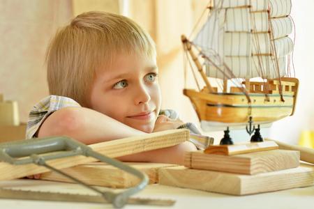 boyhood: cute little boy  working with wood in  workshop