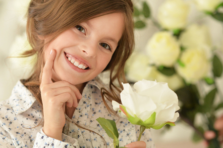 preadolescent: portrait of cute little girl posing with flower