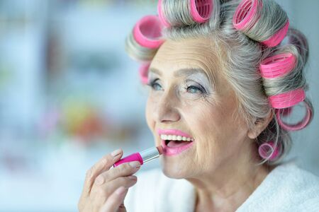 rollers: Senior woman in  hair rollers with lipstick at home Stock Photo