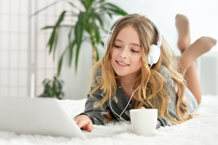 Portret van een klein schattig blond meisje met behulp van de computer Stockfoto