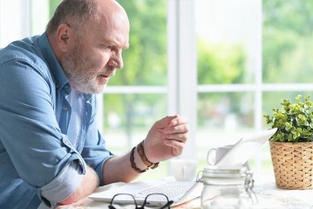 grumpy old man: Portrait of a senior man using laptop Stock Photo