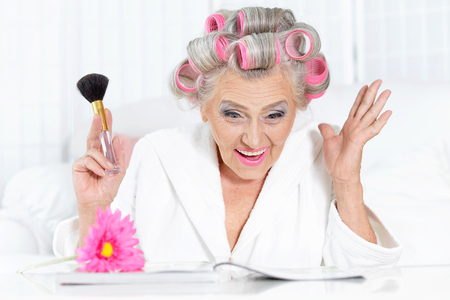 rollers: Senior woman in  hair rollers with magazine at home