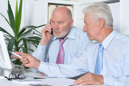 senior adults: portrait of two senior Business people working together with computer on the table