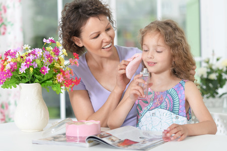 powder room: Smiling mother with little daughter  with magazine at home