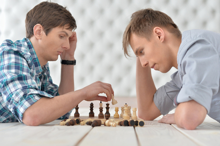 Portrait of two men playing chess at home