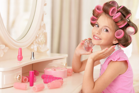 glamour makeup: portrait of happy Little pretty girl   in hair curlers with  perfume  near mirror