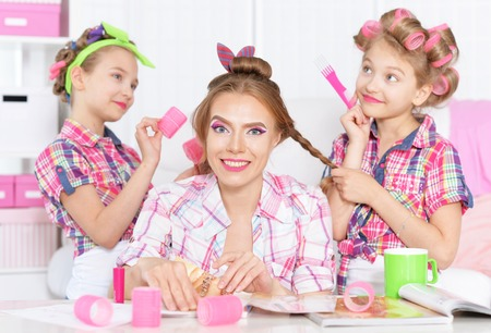 hair curlers: Cute  tweenie girls with mother   in hair curlers  doing hairstyle for their mother