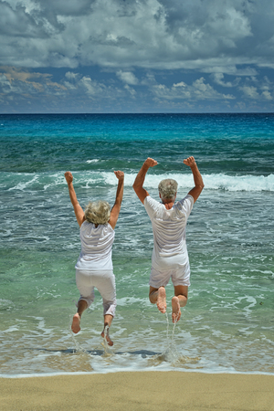 Happy Senior couple jumping in summer on  seashore Stock Photo
