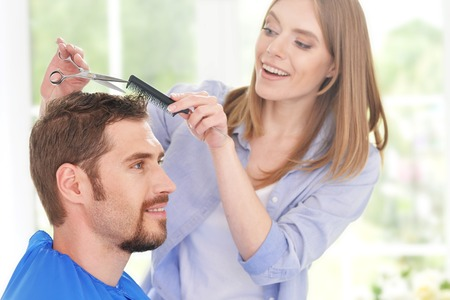 haircutter: Man having a haircut  from female hairdresser at salon Stock Photo
