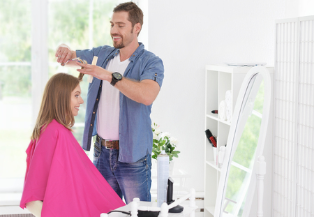 haircutter: woman having a haircut  from male hairdresser at salon