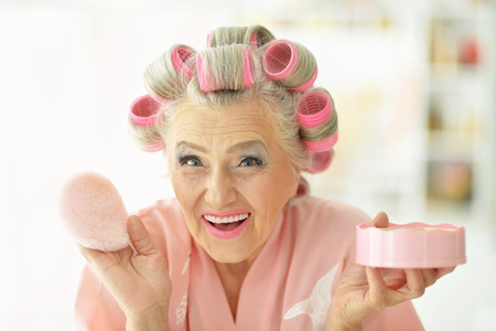 hair rollers: Senior woman in  hair rollers with powder at home