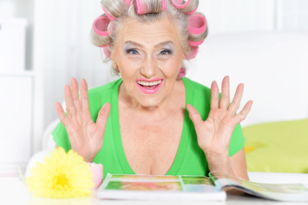 hair rollers: Senior woman in  hair rollers with magazine at home