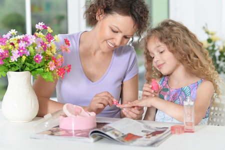 Smiling mother with little daughter  with magazine at home