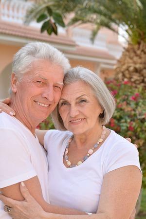 have on: Senior couple have fun near  hotel resort