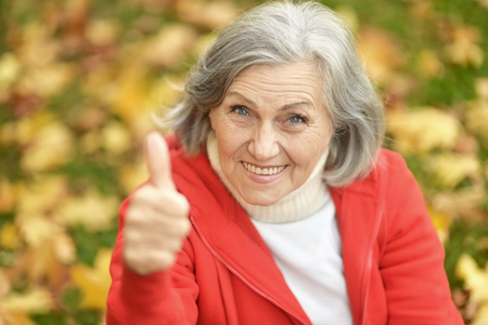 1 person: Senior woman showing thumb up in the park in autumn