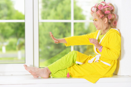 Happy cute little girl in hair curlers and nail polish