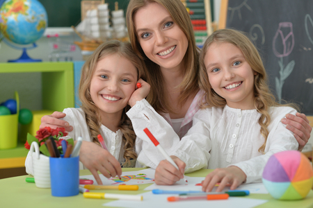 tweens: portrait of Cute girls  with mother on lesson of art