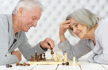 happy Senior couple resting at home and playing chess Stock Photo