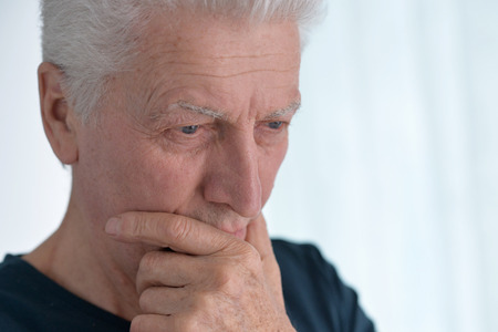 Portrait of Sad senior man at home Stock Photo