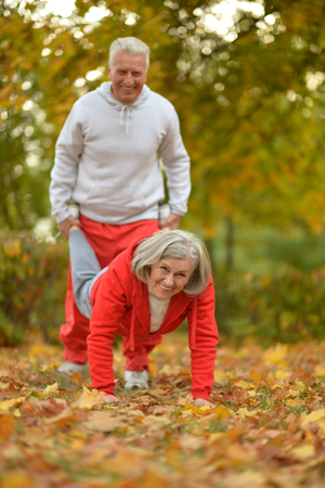 outdoor exercise: Happy fit senior couple exercising in autumn park Stock Photo