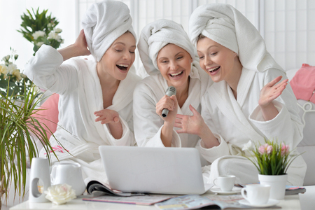 bathrobes: beautiful young women wearing a white bathrobes singing with microphone