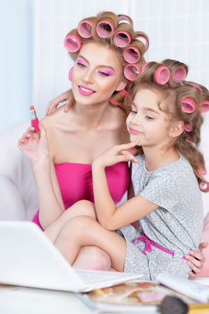 glamour makeup: portrait of happy  Mother and little daughter in hair curlers with laptop  at home