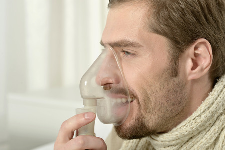 respiration: Portrait Of Man Inhaling Through Inhaler Mask