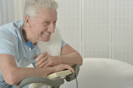 active senior man with bike in gym Stock Photo