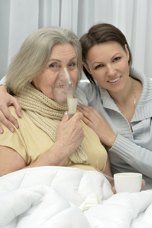 amiable: Senior ill woman with caring daughter at home