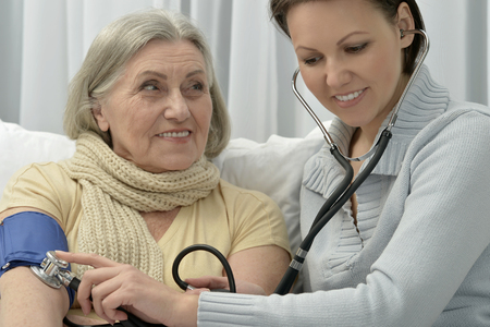 amiable: Senior ill woman with caring daughter measuring blood pressure